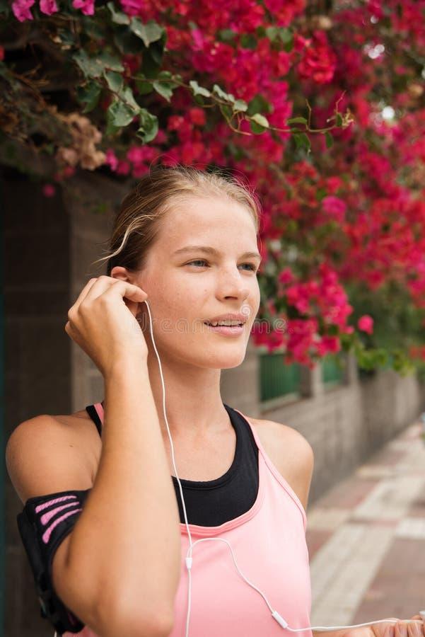 Mujer joven que ajusta los teléfonos del oído que anticipan fotografía de archivo