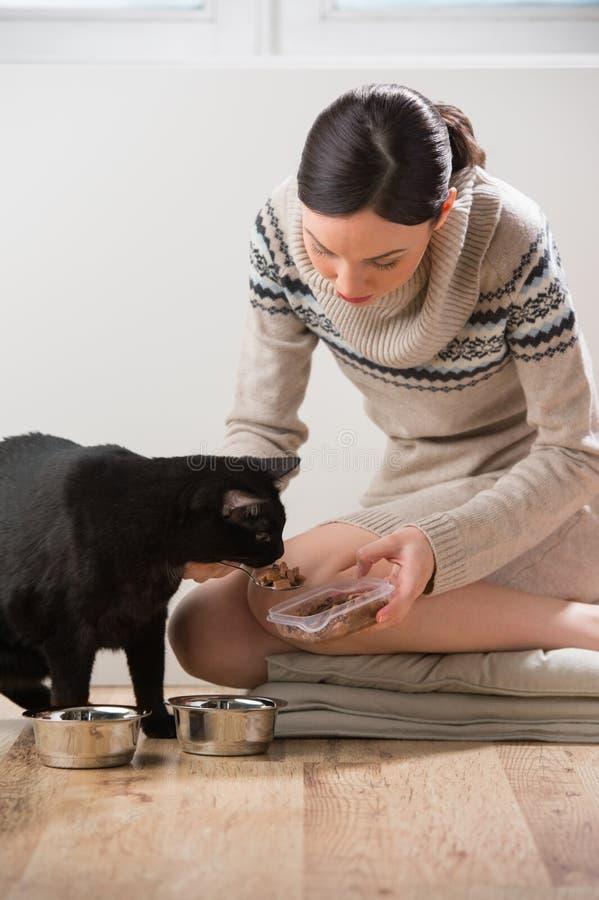 Mujer joven que alimenta su gato en casa imagen de archivo