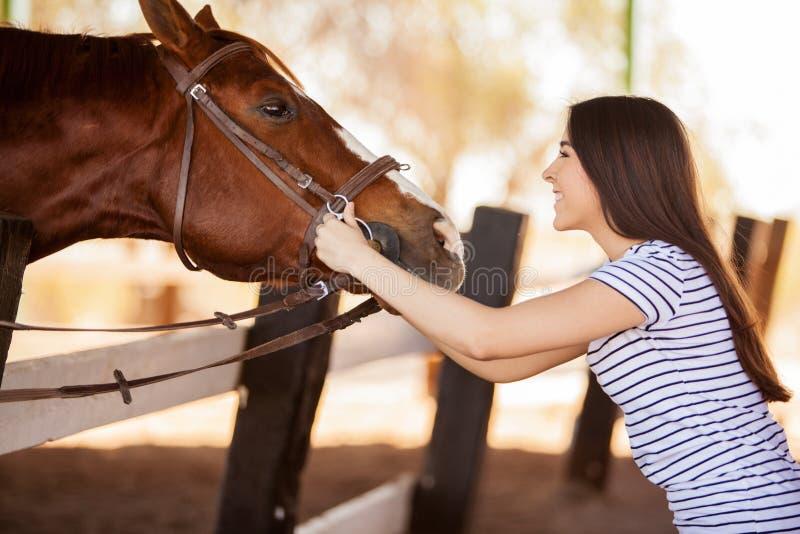 Mujer joven que ama su caballo fotos de archivo