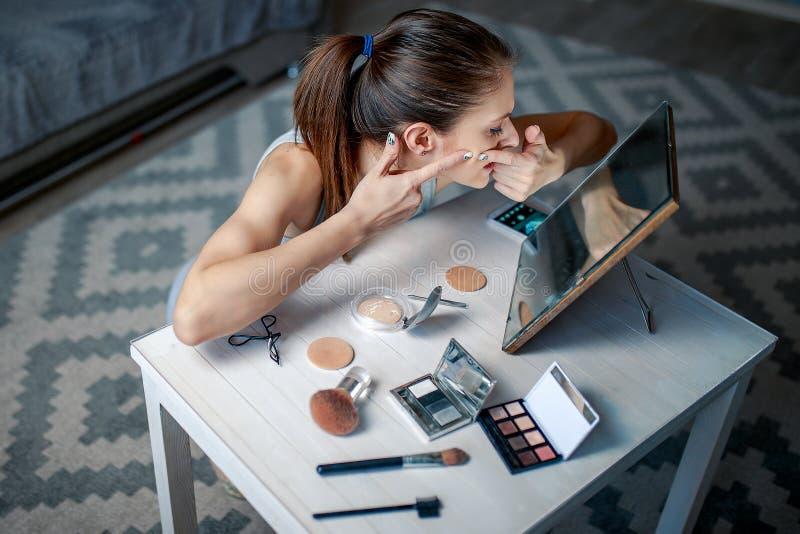 Mujer joven que aplasta espinillas antes de espejo foto de archivo