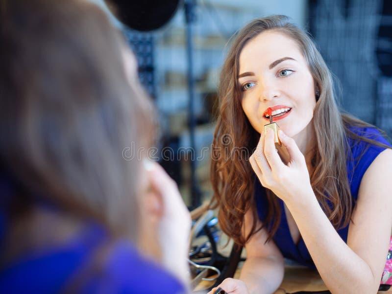 Mujer joven que aplica el lápiz labial delante de un espejo foto de archivo