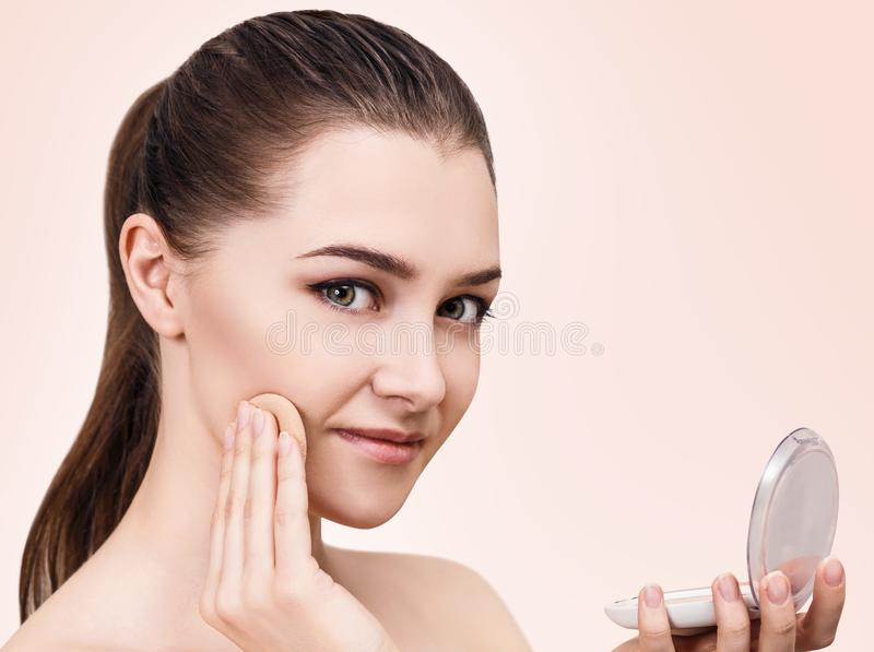 Mujer joven que aplica el polvo de los cosméticos imagenes de archivo
