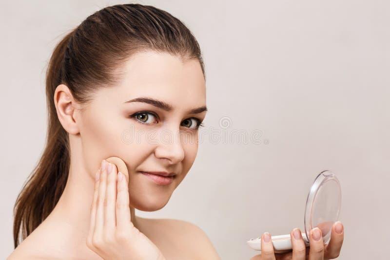 Mujer joven que aplica el polvo de los cosméticos foto de archivo