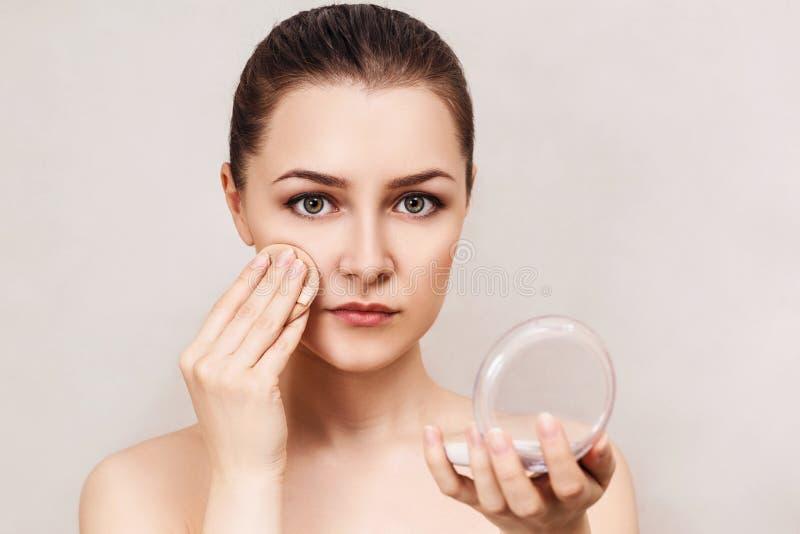 Mujer joven que aplica el polvo de los cosméticos imágenes de archivo libres de regalías