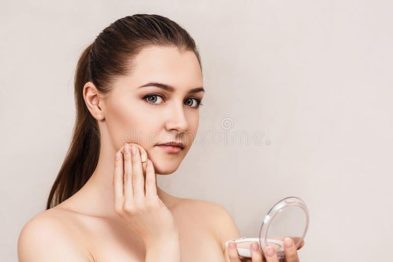 Mujer joven que aplica el polvo de los cosméticos foto de archivo libre de regalías