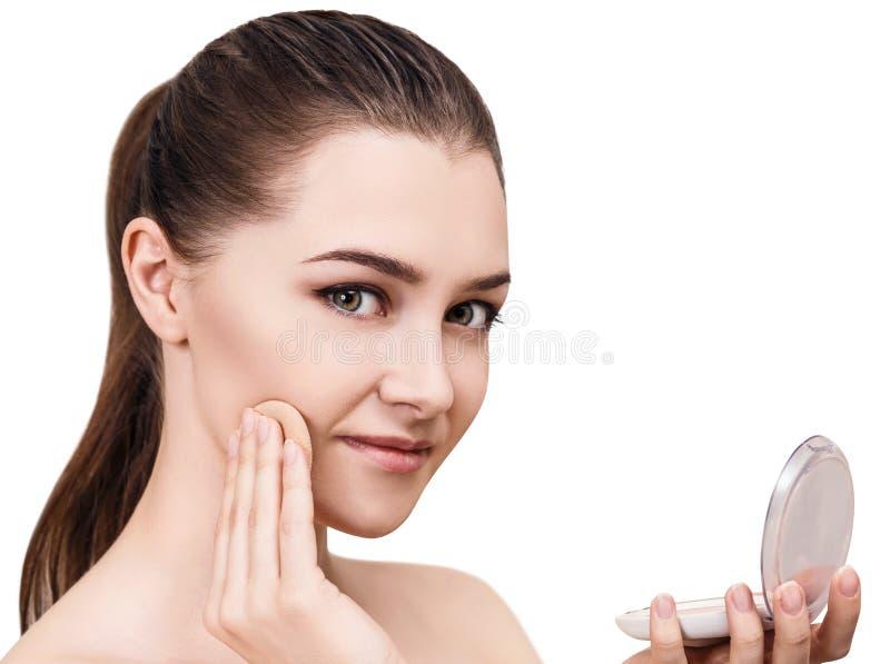Mujer joven que aplica el polvo de los cosméticos imagen de archivo libre de regalías