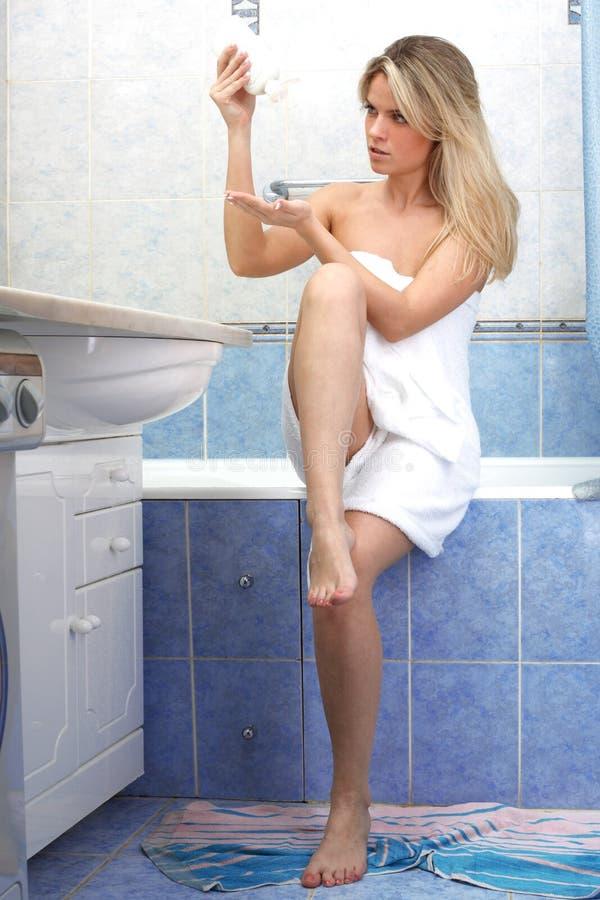 Mujer joven que aplica la crema cosmética imagen de archivo libre de regalías