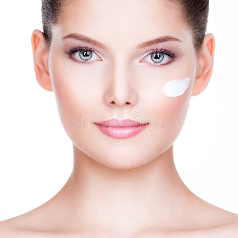 Mujer joven que aplica la crema en su cara bonita imágenes de archivo libres de regalías