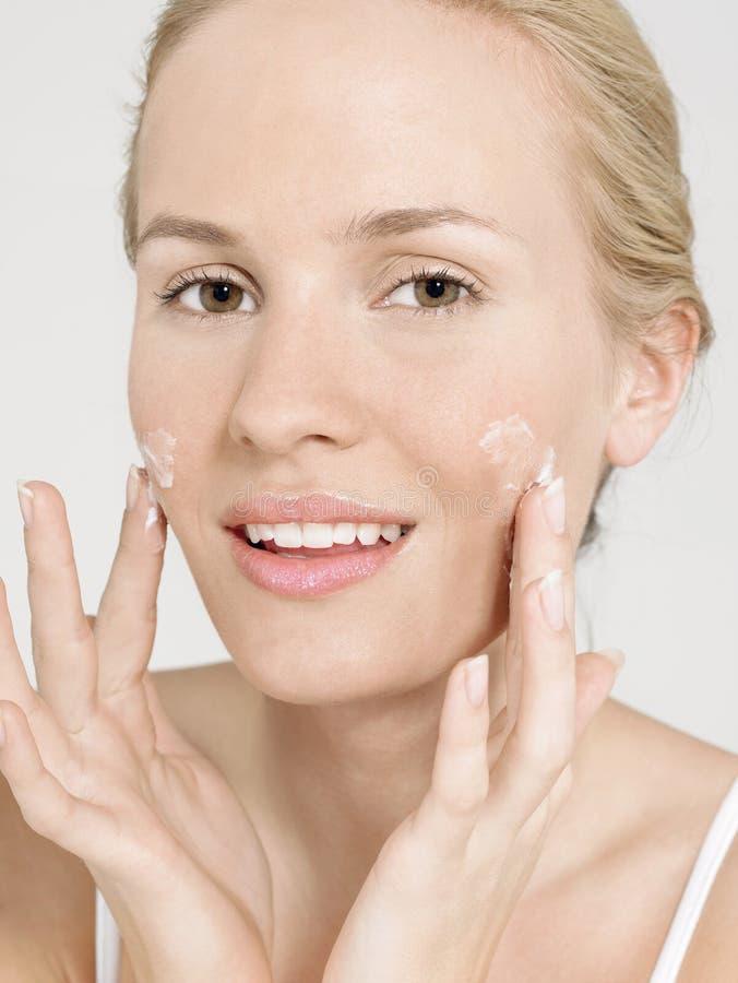 Mujer joven que aplica la crema facial foto de archivo libre de regalías
