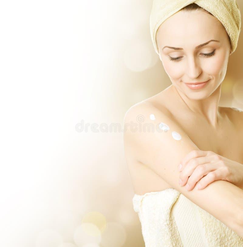 Mujer joven que aplica la crema hidratante fotos de archivo