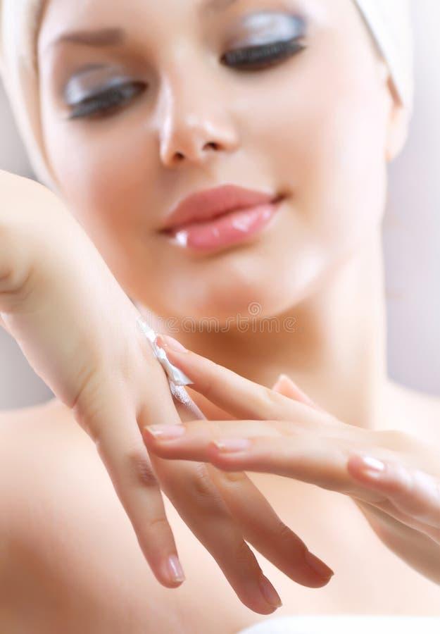 Mujer joven que aplica la crema hidratante fotografía de archivo