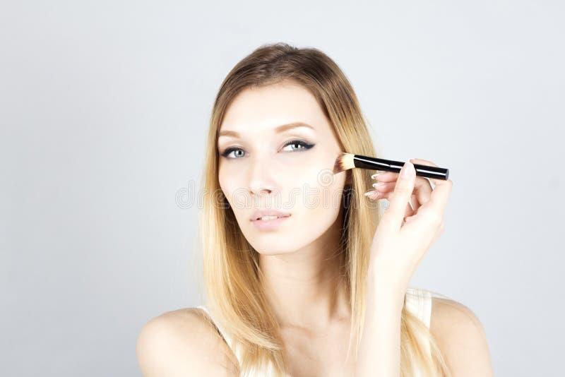 Mujer joven que aplica la fundación con el cepillo cosmético Maquillaje imágenes de archivo libres de regalías