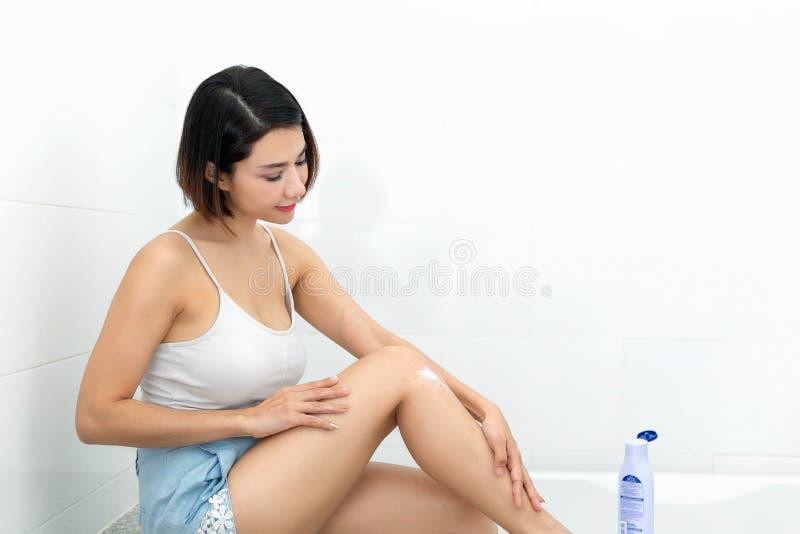 Mujer joven que aplica la loción del cuerpo en sus piernas fotografía de archivo