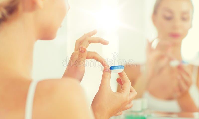 Mujer joven que aplica las lentes de contacto en el cuarto de baño imagenes de archivo