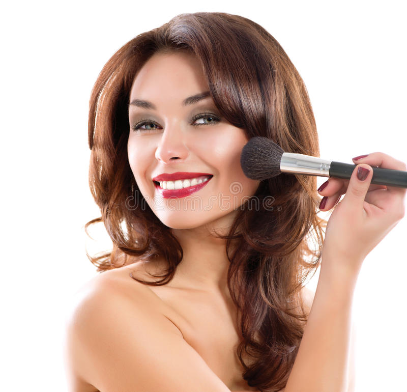 Mujer joven que aplica maquillaje imagenes de archivo