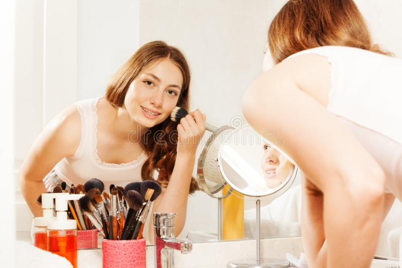 Mujer joven que aplica maquillaje con el cepillo del polvo de cara fotos de archivo
