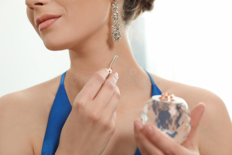Mujer joven que aplica perfume en cuello contra fondo ligero imagen de archivo