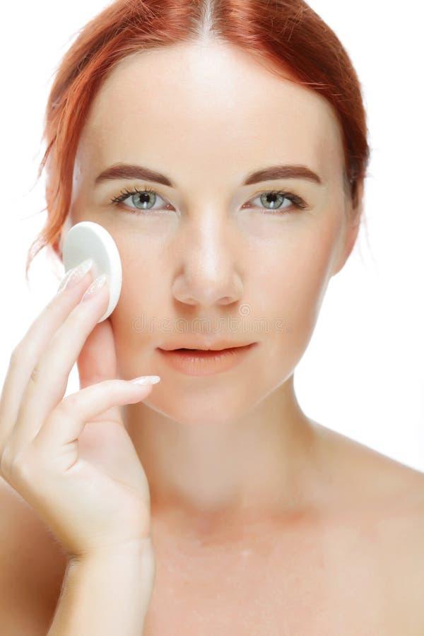 Mujer joven que aplica una nata en su cara fotos de archivo
