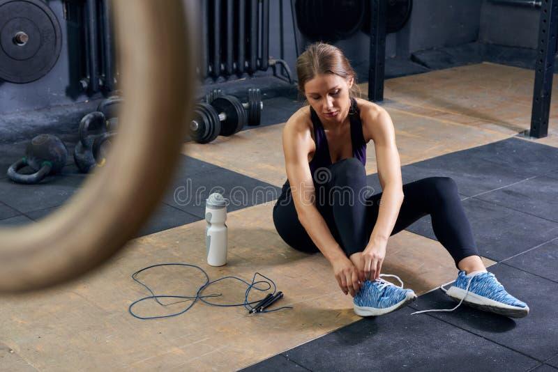 Mujer joven que ata los zapatos en gimnasio fotos de archivo libres de regalías