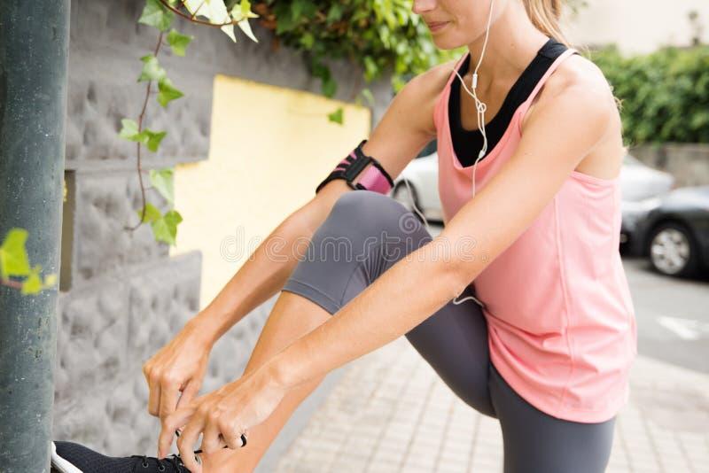 Mujer joven que ata su cordón de su zapatilla deportiva fotos de archivo libres de regalías