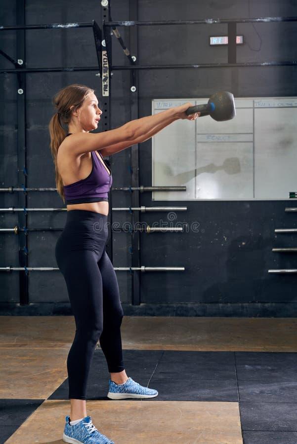 Mujer joven que balancea Kettlebell en gimnasio moderno imagen de archivo libre de regalías
