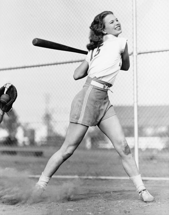 Mujer joven que balancea un bate de béisbol en un campo de béisbol (todas las personas representadas no son vivas más largo y nin foto de archivo