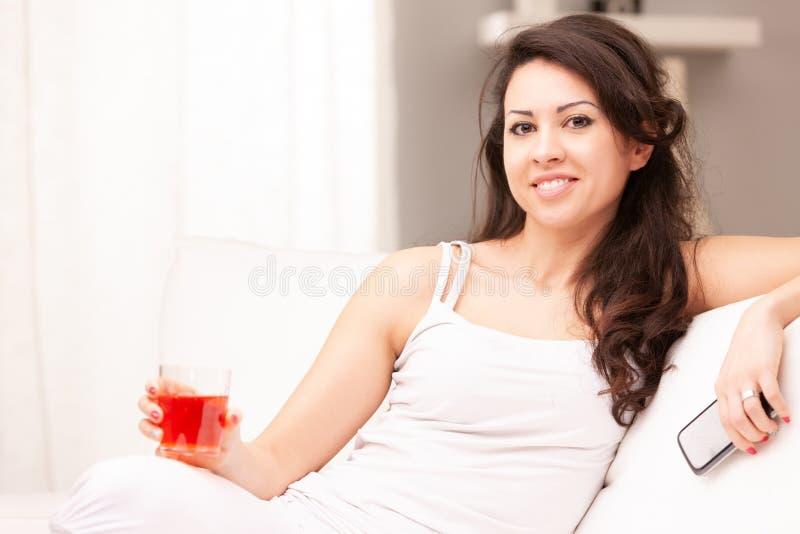 Mujer joven que bebe algo en su sala de estar imagen de archivo