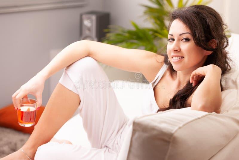 Mujer joven que bebe algo en su sala de estar fotos de archivo
