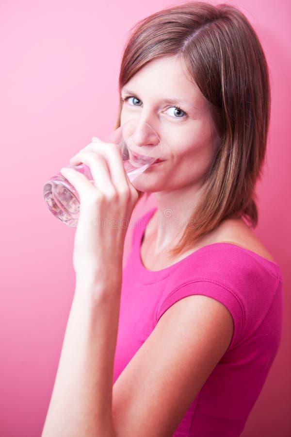 Mujer joven que bebe el agua dulce de un vidrio imagen de archivo