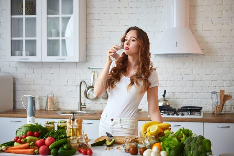 Mujer joven que bebe el agua dulce del vidrio en la cocina Forma de vida y consumici?n sanas Salud, belleza, concepto de la dieta imagenes de archivo