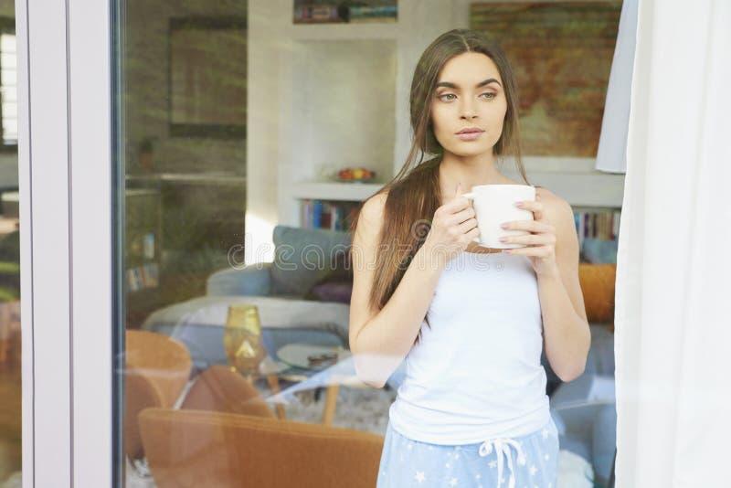 Mujer joven que bebe su té de la mañana y que sueña despierto el rato que mira a través de la ventana fotos de archivo