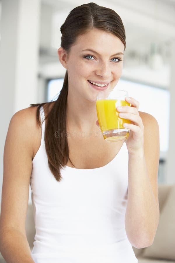 Mujer joven que bebe un vidrio de zumo de naranja fotos de archivo libres de regalías