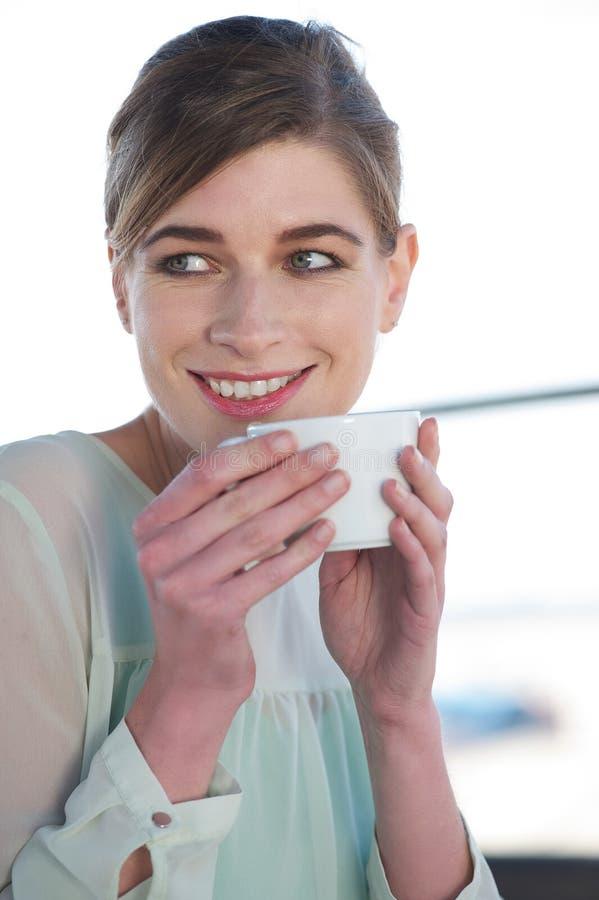 Mujer joven que bebe una taza de café al aire libre fotografía de archivo