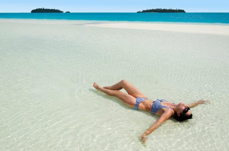 Mujer joven que broncea en el cocinero Islands de la laguna de Aitutaki fotos de archivo