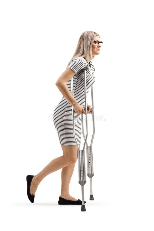 Mujer joven que camina con las muletas foto de archivo