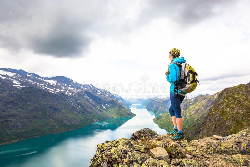Mujer joven que camina en Besseggen La muchacha feliz disfruta del lago hermoso y del buen tiempo en Noruega imagen de archivo