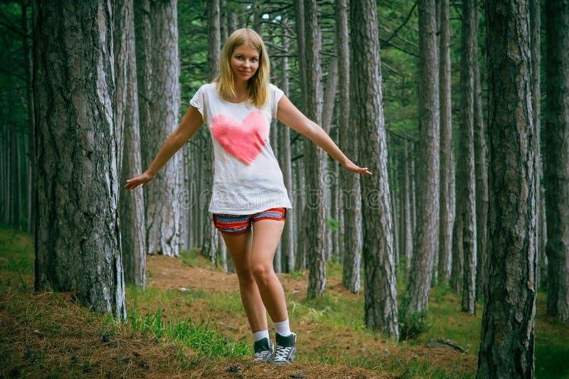 Mujer joven que camina en bosque profundo conífero fotos de archivo