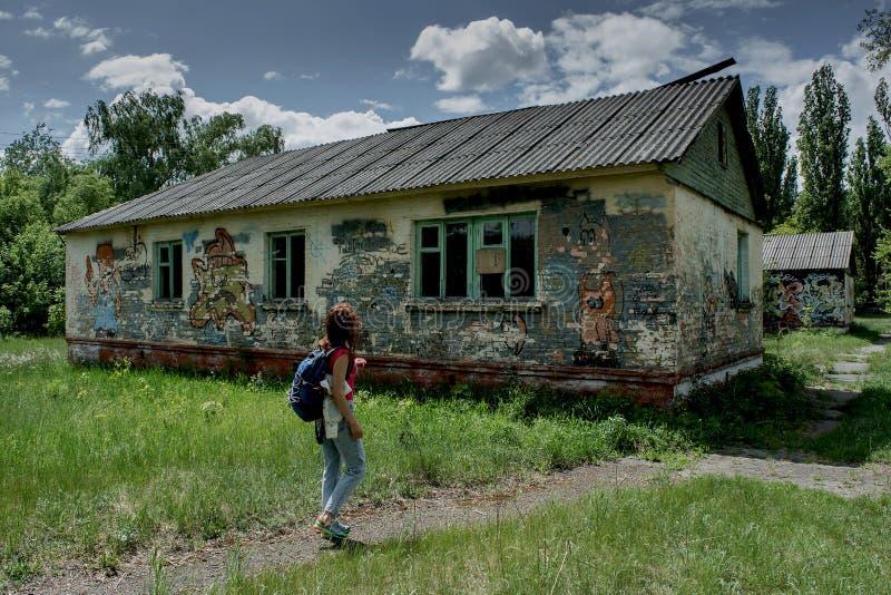 Mujer joven que camina en el camino cerca de casa abandonada espeluznante imagen de archivo