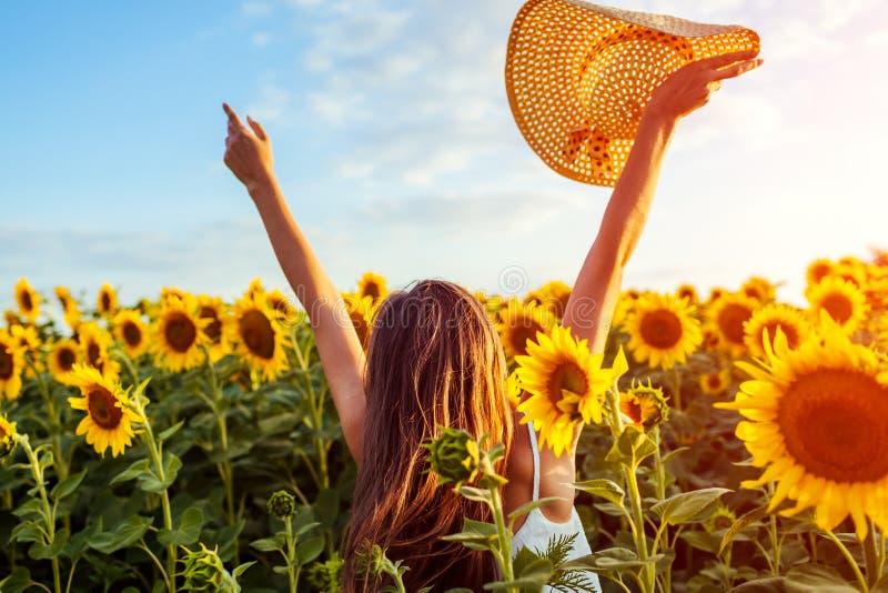 Mujer joven que camina en el campo floreciente del girasol que aumenta las manos, saltando y divirtiéndose Vacaciones de verano fotos de archivo libres de regalías