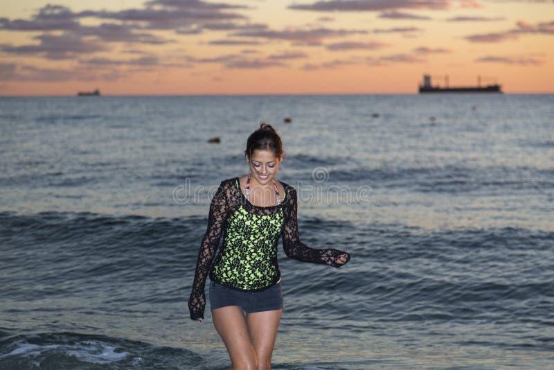 Mujer joven que camina en el océano fotos de archivo