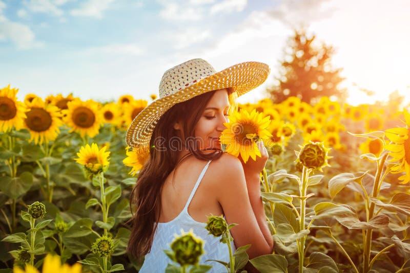 Mujer joven que camina en flores florecientes del campo y el oler del girasol Vacaciones de verano foto de archivo libre de regalías