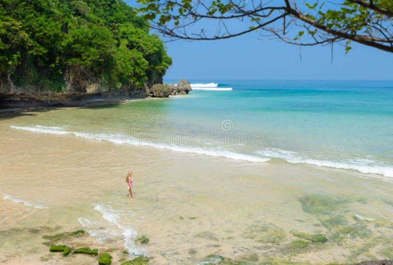 Mujer joven que camina en la playa en Bali en Indonesia imagen de archivo