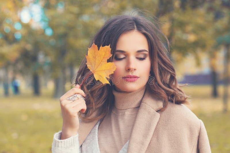Mujer joven que camina en parque del otoño y que sueña al aire libre imagenes de archivo