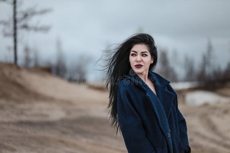 Mujer joven que camina en un desierto arenoso fr?o foto de archivo