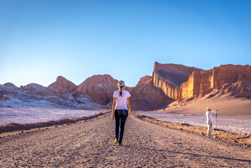 Mujer joven que camina en un paisaje surrealista en el la Luna de Valle del valle de la luna en el desierto de Atacama, Chile foto de archivo