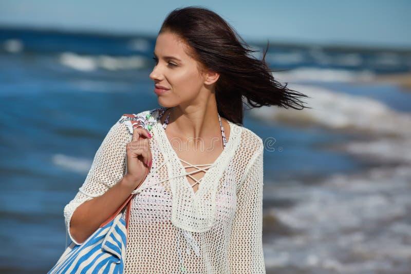 Mujer joven que camina en vestido blanco de la playa del agua que lleva foto de archivo