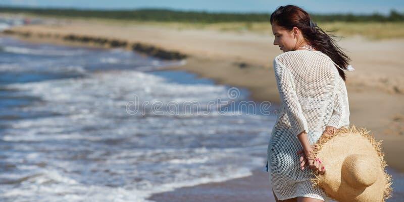 Mujer joven que camina en vestido blanco de la playa del agua que lleva imagen de archivo