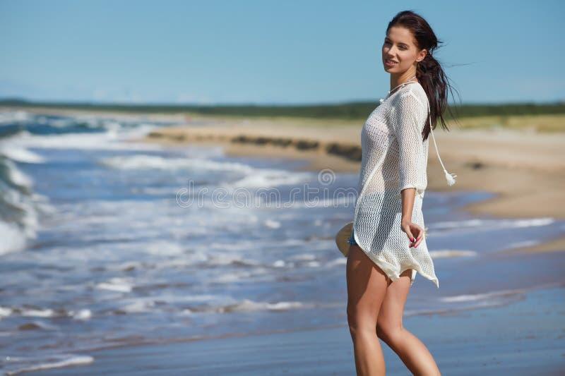 Mujer joven que camina en vestido blanco de la playa del agua que lleva imagen de archivo libre de regalías