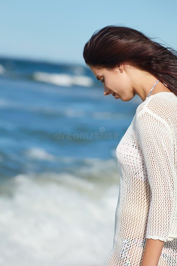 Mujer joven que camina en vestido blanco de la playa del agua que lleva fotografía de archivo