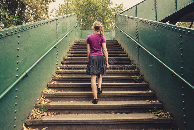 Mujer joven que camina encima de las escaleras imágenes de archivo libres de regalías